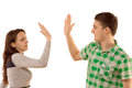 Young couple giving themselves a high fives gesture in congratulations raising their hands to slap each other on the palm isolated Royalty Free Stock Photo