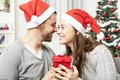 Young couple is happy with gift for christmas in front of tree Stock Images