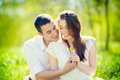 Young couple happy smiling in love lying on grass outdoor Royalty Free Stock Photography