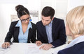 Young couple has consultation with consultant at desk at office. Royalty Free Stock Photo