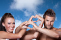 Young couple has joined hands in a heart shape on sky background with free place for text Stock Photos