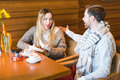 Young couple have interesting discussion in cafe Royalty Free Stock Photo