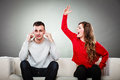 Young couple having argument conflict bad relationships angry fury women screaming men closes his ears Stock Image