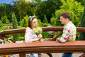 Young couple having a date on a bridge in the park Royalty Free Stock Photo