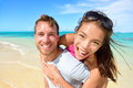 Young couple having fun laughing on beach holidays beautiful asian mixed race women piggybacking caucasian male excited at Stock Photo