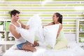 Young couple having fun with pillows at home in bedroom lot of feathers Royalty Free Stock Photo