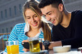 Young couple having fun with smartphones two friends in the street Royalty Free Stock Photos