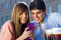 Young couple having fun with smartphones two friends in the street Royalty Free Stock Photography