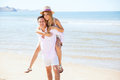 Young couple having fun together at the beach cute women piggybacking on her boyfriend while they have some on a sunny day Stock Photography