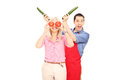 Young couple having fun with vegetables isolated on white background Royalty Free Stock Photos
