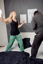 Young couple having a pillow fight enjoying themselves standing on bed Stock Image