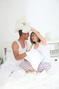 Young couple having a pillow fight playful sitting on top of the bedclothes on their bed in their sleepwear Royalty Free Stock Photos