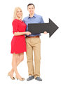 Young couple holding a big black arrow full length portrait of pointing right isolated on white background Stock Images