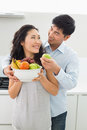 Young couple holding bowl full of fruit in kitchen men and women the at home Stock Photos