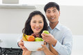Young couple holding bowl full of fruit in kitchen portrait a men and women the at home Stock Photo