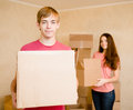 Happy young couple packs cardboard boxes for moving into a new house