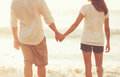 Young Couple Holding Hands on the Beach at Sunset Royalty Free Stock Photo