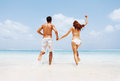 Young couple holding hands going for a swim Stock Photos