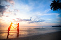 Young couple holding hands heart-shaped on the sea beach Royalty Free Stock Photo