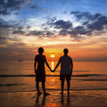 Young couple holding hands on ocean coast during the amazing sunset. Royalty Free Stock Photo