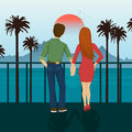 Young couple holding hands standing on seafront, looking at sunset. Mountains, sea, ocean, palm trees, seacoast