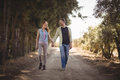 Young couple holding hands while walking on dirt road at olive farm Royalty Free Stock Photo