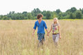 Young couple holding hands while walking through field Royalty Free Stock Photo