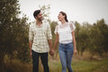 Young couple holding hands while walking on field at farm Royalty Free Stock Photo
