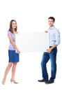 Young couple holding a placard over white background Stock Photos