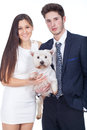 Young couple holding a white dog Stock Image