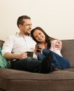 Young couple in home interior cheerful on a sofa Royalty Free Stock Images