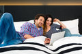Young couple in hotel in bed with wifi and computer lying the of a room they are on vacation using the the room for internet the Stock Photo