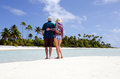 Young couple hugs on deserted tropical island male and female the white sand of a in aitutaki lagoon cook islands Stock Photo