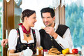 Young couple in a hunter s cabin eating traditional mountain hut having hearty breakfast Stock Photo