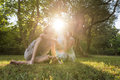 Young couple in an intimate bonding moment with their baby strong sun flare obscuring faces of wearing summer clothes sitting on Royalty Free Stock Image