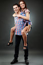 Young couple joyful lovers with a piggyback ride studio shot Royalty Free Stock Image