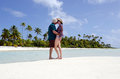 Young couple kisses on deserted tropical island male and female the white sand of a in aitutaki lagoon cook islands Royalty Free Stock Image