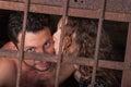 Young couple kissing behind bars