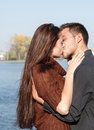 Young couple kissing lake and trees on background Stock Photography
