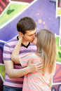 Young couple kissing near graffiti background. Royalty Free Stock Photo