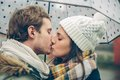 Young couple kissing outdoors under umbrella in a