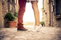 Young couple kissing outdor outdoors lovers on a romantic date at sunset girls stands on tiptoe to kiss her men close up on shoes Royalty Free Stock Photo