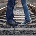 Young couple kissing at railways rails two people standing in love summer day Royalty Free Stock Photos