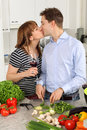 Young couple kissing in their kitchen Royalty Free Stock Photography