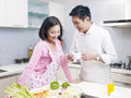 Young couple in kitchen asian talking Royalty Free Stock Photo