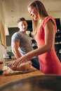 Young couple in kitchen preparing food shot of standing women cutting bread with men standing by focus on women breakfast Stock Photos