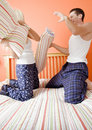 Young Couple Kneeling on Bed Having a Pillow Fight Stock Photos
