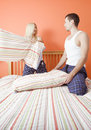 Young Couple Kneeling on Bed Having a Pillow Fight Royalty Free Stock Photos