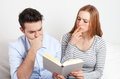 Young couple learning with a book student foreign language at home on sofa Royalty Free Stock Photos