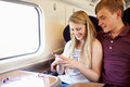 Young couple listening to music on train journey relaxing Stock Image